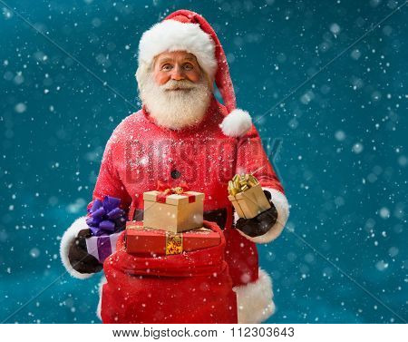 Happy and kind Santa Claus with christmas present