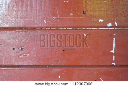 Closeup of red wooden texture of board with scarp of paper.