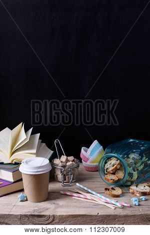Still life coffee to go with cookies and books on wooden table, black wall.Hipster style, copy space