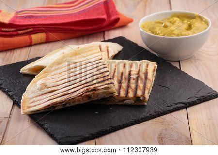 Quesadilla and Guacamole on a rustic table