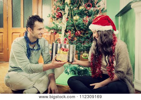 Happy Couple Exchanging Gifts At Home By Christmas Tree
