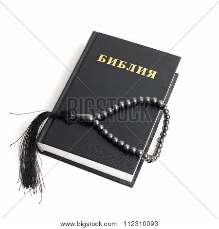 Bible with rosary, white background