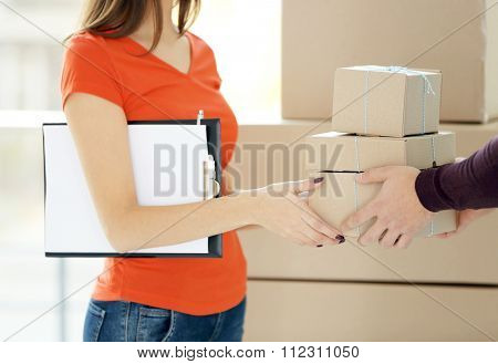 Young man receiving parcel from delivery worker, close up