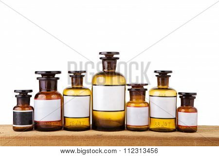 Various Vintage Pharmacy Bottles With Blank Labels On Wooden Board