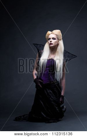 Beautiful blonde girl vampire standing on the knees