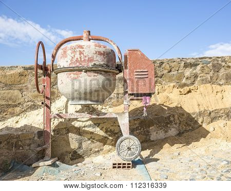an electric cement Mixer on the floor and a blue sky