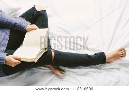 Woman in black jeans reading book on bed top view point