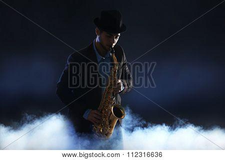 Elegant saxophonist plays jazz on dark background in a smoke