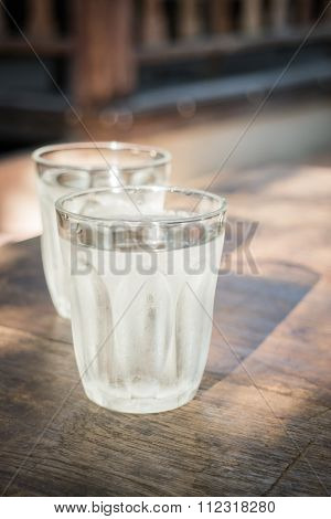 Double Glasses Of Cold Water On Wooden Table