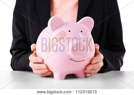 Woman holding Piggy Bank with adhesive bandage, on white background
