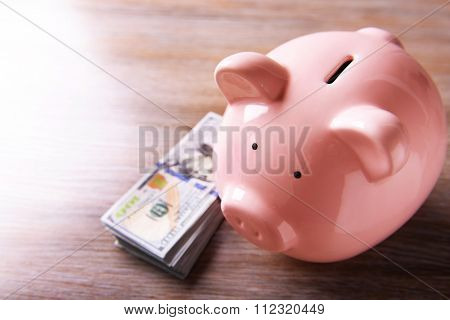 Pig moneybox and dollar banknotes on light background
