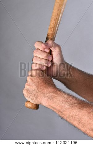 Closeup of a baseball batters hands holding a wood bat. Vertical format against a gray background.