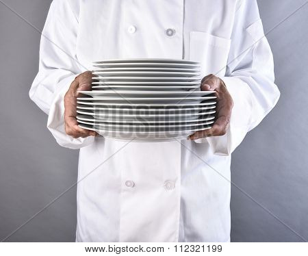 Closeup of a chef holding a stack of white plates. The man is unrecognizable. Square format against a gray background.