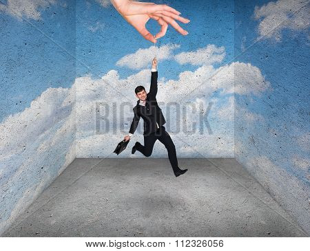 Big hand holding businessman in rough room