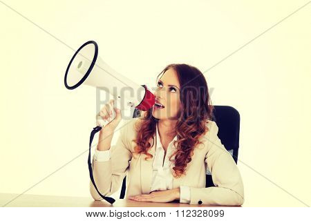 Businesswoman shouting with megaphone by a desk.