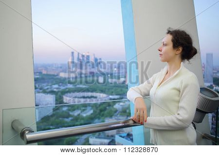 young girl standing on top floor of tall building and watching from the balcony