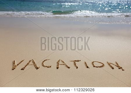 Vacation written in the sand on the beach, blue waves on background