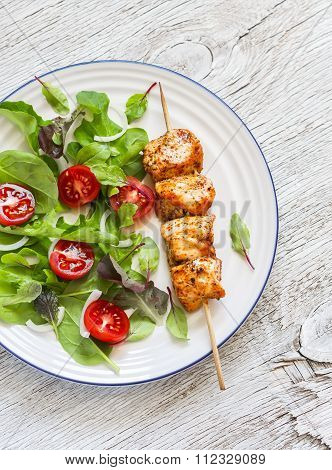 Chicken Kebab And Fresh Vegetable Salad On A Light Wooden Background