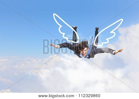 Young businessman with drawn wings flying in sky