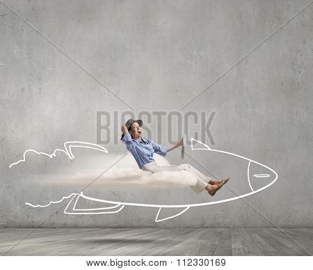 Young happy student girl riding fast drawn rocket