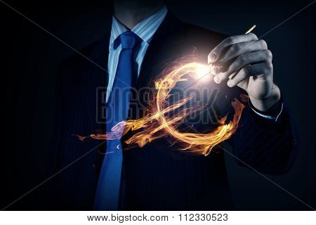 Close view of businessman drawing on screen burning euro sign