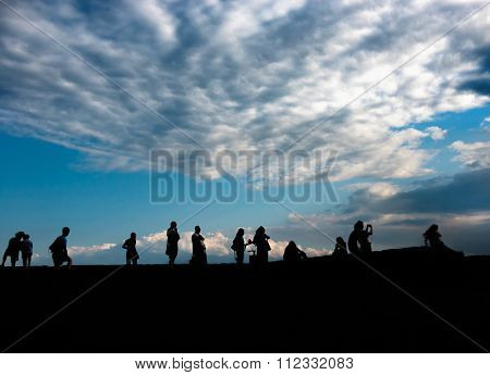 silhouettes of people admiring sunrise in scenic place in Ukraine