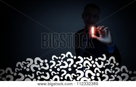 Young  businessman on dark background taking exclamation mark with fingers