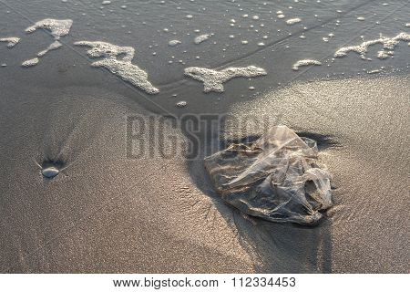 Used plastic bag garbage on sand beach