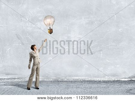 Businesswoman reaching hand to touch glass glowing light bulb