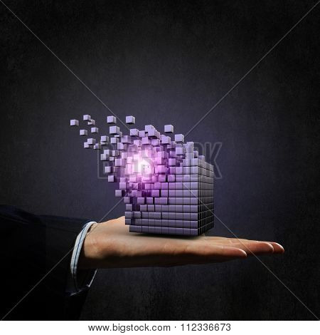 Businessman hand shows disintegrating cube in palm