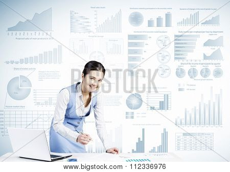 Businesswoman standing at table and writing with pen and infographs at background