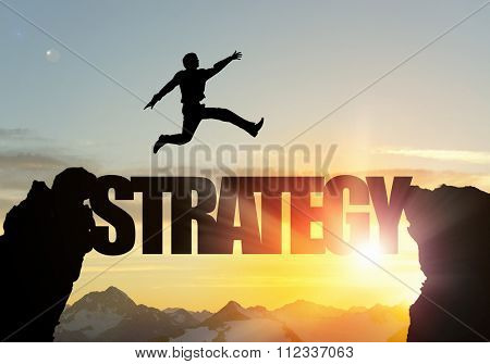 Businessman running on strategy word bridge over precipice