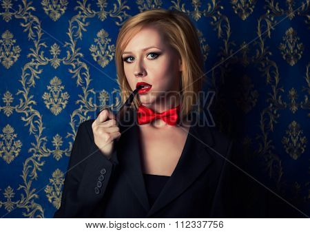Young blonde with red lips and smoking pipe wearing suite