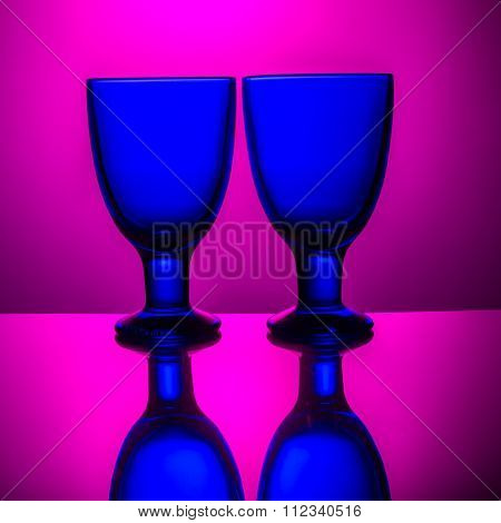 Couple of blue glasses on a pink background
