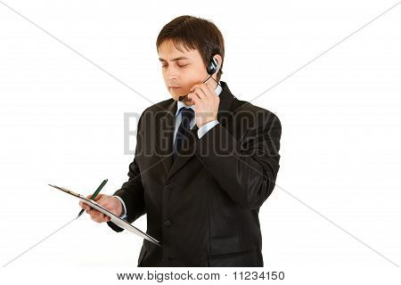 Thoughtful young businessman with headset and clipboard isolated on white