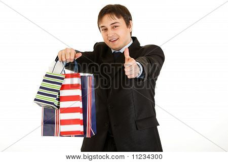 Smiling young businessman holding shopping bags and showing thumb up gesture isolated on white