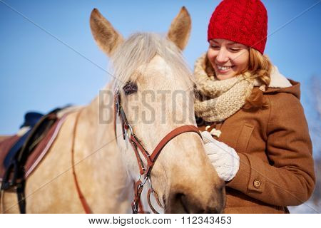 Pretty woman petting horse in the farm