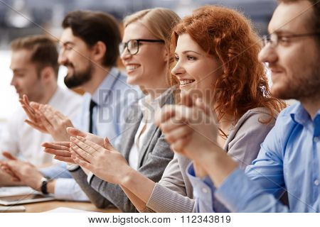 Group of business people sitting together at the table and applauding