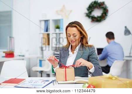Young businesswoman unpacking gift-box in office