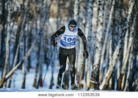 male athlete skiers race in winter forest classic style riding uphill