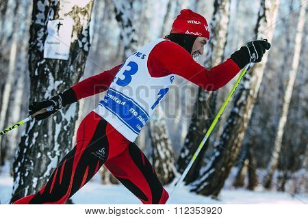 closeup male skier middle-aged of classic style in winter woods on sports race