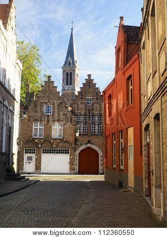 medieval buildings on cobblestone street with garage and cathedral in historic Brugge Bruges Belgium Europe