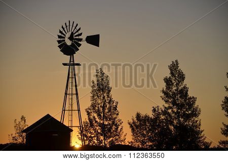 Windmill and shed silhouetted in sunrise