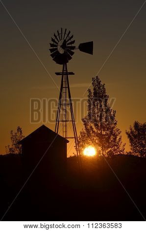 Silhouette of windmill and shed