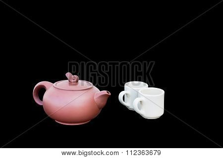 Red Teapot And White Teacups Isolated On Black Background