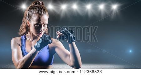 Portrait of female confident boxer with fighting stance against desert landscape