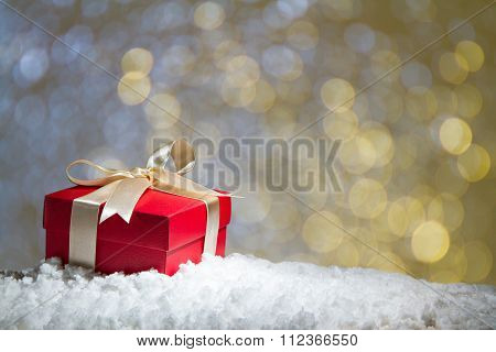 Red Gift Box On Snow With Abstact Bokeh Background.