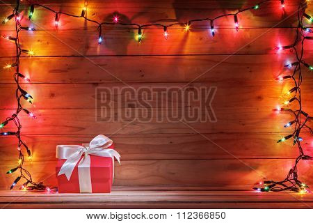 Gift Box With Christmas Light And Wooden Background.
