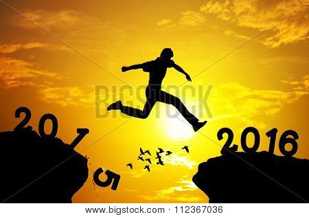 Man Jumping Over Precipice On Sunset Background