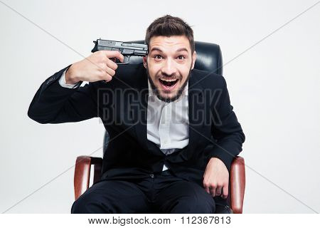 Crazy hysterical bearded young businessman sitting on black office chair and put gun to his temple over white background